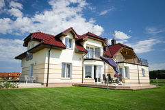 Elegant suburban house. A picture of a two-storey house with attic, surrounded by a neat lawn Stock Photography