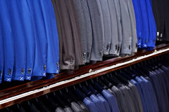Elegant suits in a row inside suit store Stock Image