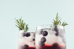 Elegant summer fresh drinks with ice cubes, blueberry, rosemary on fashion pastel mint color background, closeup, top section. Elegant summer fresh drinks with stock photo