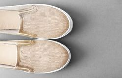 Elegant summer moccasins close up. Women`s golden moccasins close up. Lightweight comfortable summer shoes on a gray background top view Stock Photo