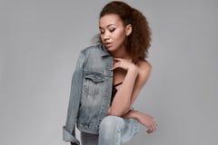 Elegant svart kvinnamodell för glamour i jeans och omslag Royaltyfri Foto