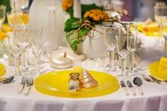 Elegant tabelluppsättning i mjuk kräm och guling för att gifta sig eller händelse royaltyfria foton