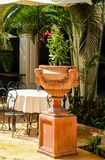 Elegant table outside under umbrella with tropical foliage and flower urn. An Elegant table outside under umbrella with tropical foliage and flower urn Stock Photo