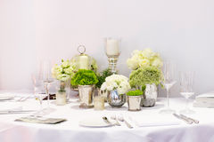 Elegant table set in green and white for wedding or event party. Royalty Free Stock Images