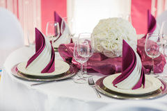Elegant table set in soft creme for wedding or event party. Beautiful elegant table set  for wedding or event party in dark red and white with flowers, indoors Royalty Free Stock Photo