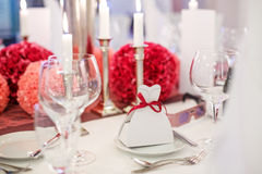 Elegant table set  for wedding or event party in soft red and pi. Nk, with paper bride and groom Stock Photos