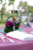 Elegant table setting. Elegant outdoor table setting with purple tablecloth and flowers royalty free stock photo