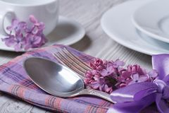 Elegant table setting for breakfast, with flowers lilacs Stock Image