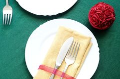 Elegant table setting for Christmas dinner. Top view holidays table setting. On a green tablecloth white dish, fork, lnife, napkin, an a red candle Royalty Free Stock Photos