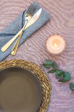 Elegant table setting on purple linen cloth dark plate rattan coaster cutlery blue napkin, burning candle. Twig of silver dollar eucalyptus, top view, flatlay Royalty Free Stock Image