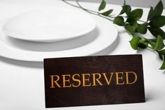 Elegant table setting and RESERVED sign in restaurant. Closeup stock photo