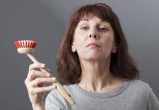 Elegant 50-talkvinna som räcker över maträttborsten för tvätt och att göra ren hemma Arkivbilder