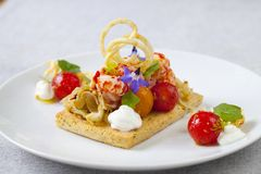 Elegant tart with crayfish. Thyme tart with crayfish, goat cheese mousse, fennel, tomatoes and crispy potato stock photo