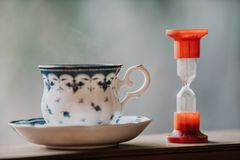 Elegant tea cup and hourglass stand shelf. Time to drink tea. A neat cup for tea with a blue pattern and a saucer stand on wooden rails. Near the hourglass Stock Image