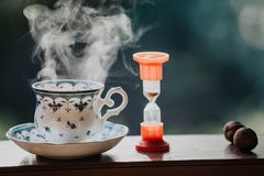Elegant tea cup and hourglass stand shelf. Time to drink tea. A neat cup for tea with a blue pattern and a saucer stand on wooden rails. Near the hourglass Stock Photos