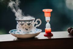 Elegant tea cup and hourglass stand shelf. Time to drink tea. A neat cup for tea with a blue pattern and a saucer stand on wooden rails. Near the hourglass Stock Photo