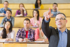 Elegant teacher and students at the college lecture hall. Elegant teacher pointing away with students sitting at the college lecture hall Royalty Free Stock Photography