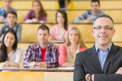 Elegant teacher with students sitting at lecture hall Stock Images