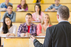 Elegant teacher with students sitting at the lecture hall Royalty Free Stock Image