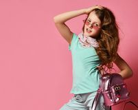 Elegant high society girl teen in sunglasses, fashion scarf and with shiny backpack looks at us with her hand in her hair. Elegant teen girl, high society young royalty free stock photography