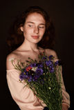 Elegant tender redhead girl holding bouquet of wild flowers Royalty Free Stock Image