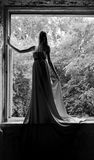 The elegant thin  woman in a long dress. Stands in the big window of ruined structure Stock Images