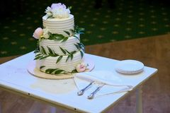 Elegant three-tiered white wedding cake decorated with natural flowers or roses and green leaves on a white wooden table. Nearby stock images