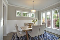 Elegant transitional dining room with board and batten walls. Wood dining table surrounded by grey upholstered dining chairs royalty free stock image