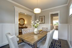 Elegant transitional dining room with board and batten walls. Wood dining table surrounded by grey upholstered dining chairs stock image