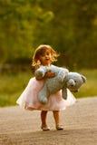 Elegant två-år-gammal flicka som bär det välfyllda djuret Arkivfoto