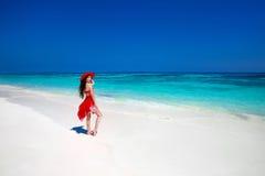 Elegant tyckande om kvinna i röd hatt och klänning som vilar på tropiskt Royaltyfria Foton