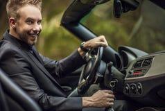 Elegant ung attraktiv man i den utomhus- konvertibla bilen. Fotografering för Bildbyråer