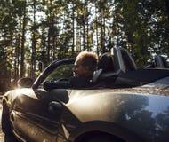 Elegant ung attraktiv man i den utomhus- konvertibla bilen. Royaltyfri Foto