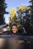 Elegant ung attraktiv man i den utomhus- konvertibla bilen. Arkivfoto
