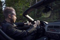 Elegant ung attraktiv man i den utomhus- konvertibla bilen. Arkivfoton