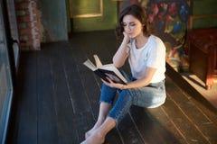 Elegant ung brunettflicka som läser ett boksammanträde på golvet i rummet Den stilfulla inre och solen att glo, hemtrevlig tidsfö arkivbild