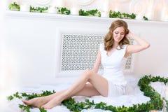 Elegant ung flicka som sitter visa försiktigt hennes långa ben som ner shyly ler, vit torkduk under henne som kontrasterar med ny royaltyfri fotografi