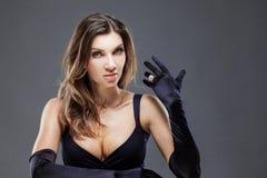 Elegant ung kvinna i långa svarta handskar Kvinna med en härlig cirkel, smycken Royaltyfri Foto