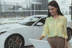 Elegant ung kvinna som köper den nya bilen på återförsäljaren royaltyfri fotografi