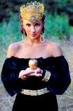 Elegant ung kvinna som kläs som drottning Royaltyfri Bild