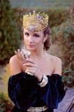Elegant ung kvinna som kläs som drottning Royaltyfri Foto