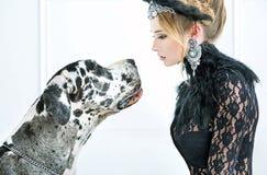 Elegant ung kvinna som stirrar på hunden royaltyfria bilder