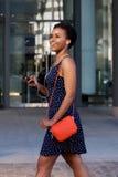 Elegant ung kvinna som utanför går med mobiltelefonen och hörlurar arkivbilder