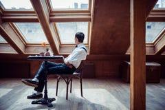 Elegant ung man i hängslen och exponeringsglas i kafé arkivfoto