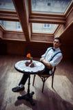 Elegant ung man i hängslen och exponeringsglas i kafé arkivfoton