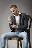 Elegant ung man i sammanträde på en stol, medan knäppas hans sle Arkivbilder
