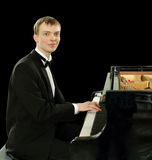 Elegant ung pianist av flygeln Arkivfoto