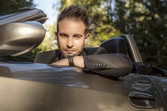 Elegant ung positiv man i den utomhus- konvertibla bilen. Arkivbilder