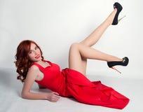 Elegant ung rödhårig mankvinna i en röd klänning och svarta höga häl som ligger på hans baksida och sätter hans fot upp Royaltyfria Foton
