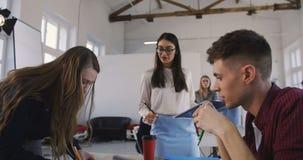 Elegant ung säker kvinna för lagledare i exponeringsglas som ger anvisningar till multietniska kollegor i modernt kontor arkivfilmer